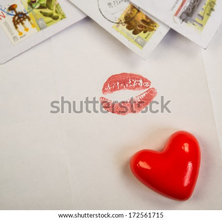 red valentine heart lies on a background of open letters and envelopes  - stock photo