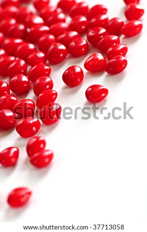 Red Valentine's cinnamon heart candies on white background