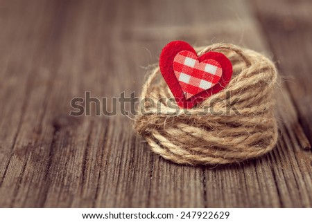 Red valentine's day holiday heart in nest on wooden background with retro instagram toning - stock photo