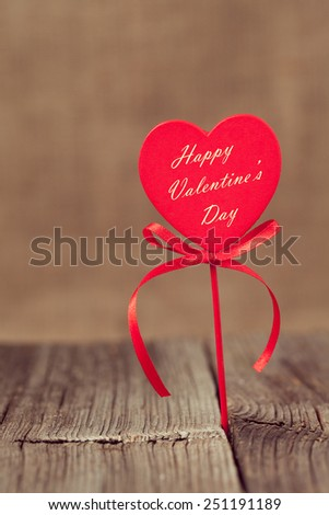 Red valentine's day holiday heart on stick  on retro wooden background with vintage instagram toning - stock photo
