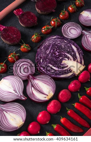 Red vegetables cut in halves, flat lay design on dark background, symmetric. - stock photo