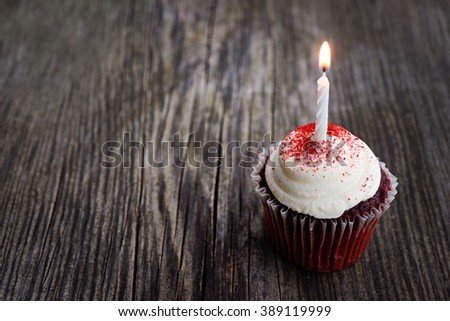 Red Velvet birthday cupcake with candle on wood background - stock photo