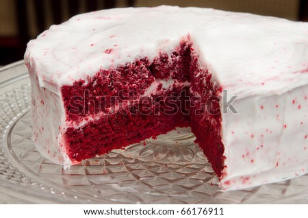 red velvet cake on a glass platter with one slice removed - stock photo
