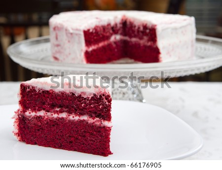 red velvet cake on a glass platter with one slice removed in front - stock photo