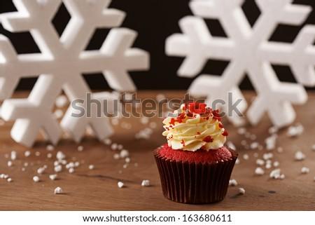 Red velvet cupcake on white snow flakes Christmas background - stock photo