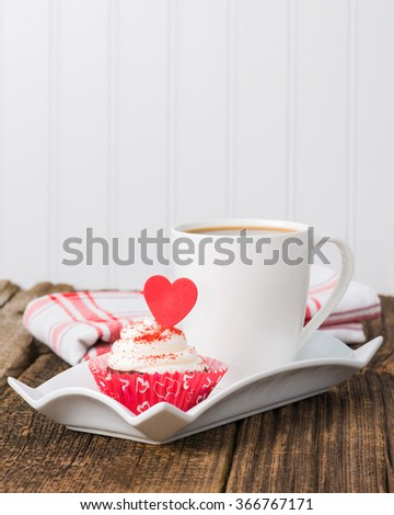 Red velvet cupcake served with a cup of coffee. - stock photo