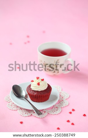 Red Velvet Cupcake with Cream Cheese Frosting decorated with sugar hearts, on a little plate, silver spoon and cup of fruit tea, on a pink background. - stock photo