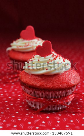 Red velvet cupcakes with a red heart on top on a red background - stock photo