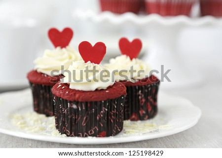 Red velvet cupcakes with cream cheese frosting decorated with chocolate hearts