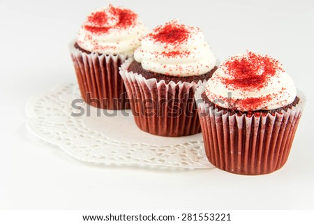 red velvet cupcakes with white frosting and red sprinkles