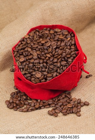 Red velvet sac with coffee beans - stock photo