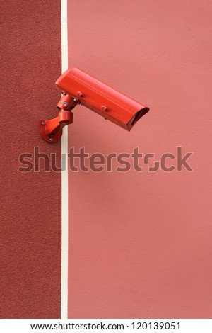Red video Camera Security System on the wall - stock photo