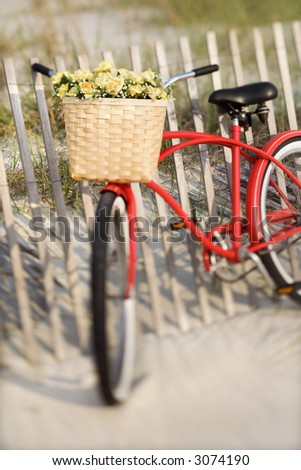 Red vintage bicycle with basket and flowers leaning against wooden fence at beach. - stock photo