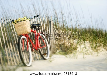 Red vintage bicycle with basket and flowers lleaning against wooden fence at beach. - stock photo