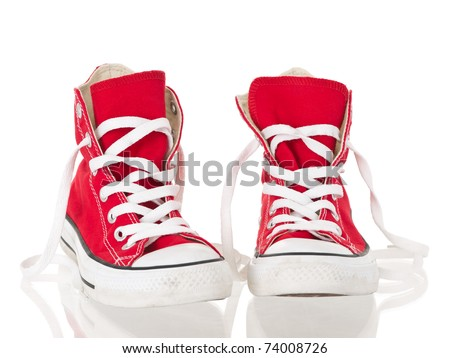 Red vintage canvas sneakers untied on white background - stock photo