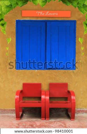 Red vintage chairs against orange wall with leaf - stock photo