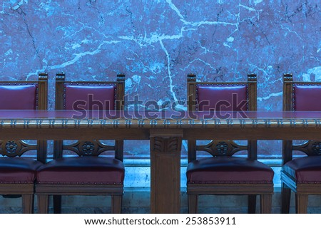 Red Vintage chairs by the old wooden conference table with a blue marble background wall.  - stock photo