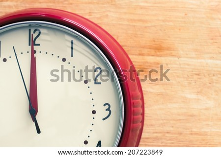 Red vintage clock about to strike 12 midnight or midday, possibly conceptual of New Year. - stock photo