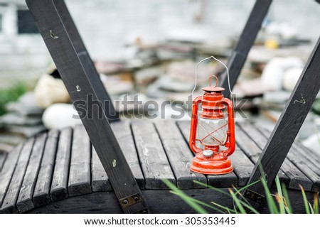 Red vintage kerosene lamp isolated on garden background - stock photo