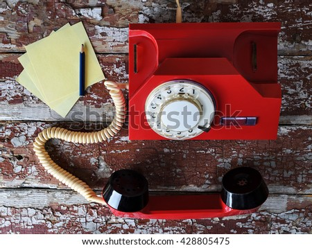 Red vintage phone on wooden background with pencil close-up, top view, pick up the phone - stock photo