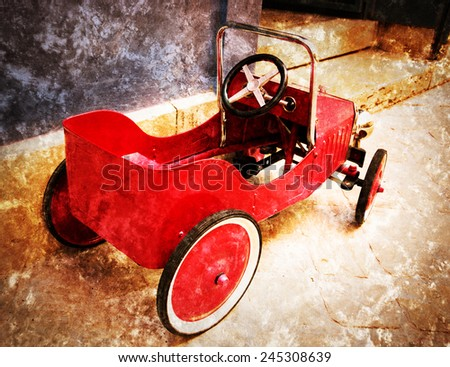 Red vintage toy car near entrance to the house. Back and side view. Retro aged photo with scratches. - stock photo