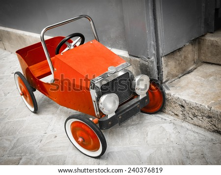 Red vintage toy car near entrance to the house. Front and side view. Aged photo.  - stock photo