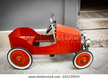 Red vintage toy car near entrance to the house. Side view. Aged photo.  - stock photo