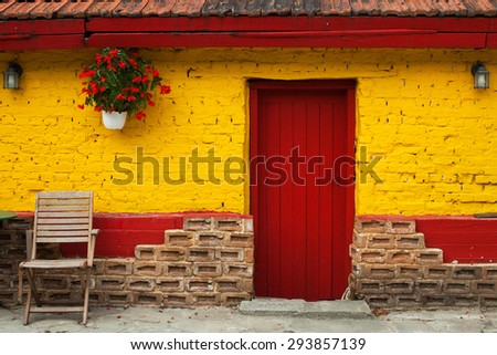 Red Vintage wooden door in yellow rural wall. Background texture.Facade of an old house with vintage door.Colored Background - stock photo