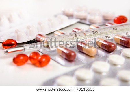 red vitamins and pills in boxes and thermometer