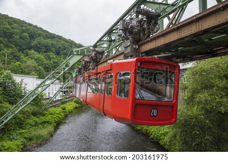 Red wagon of Wuppertal Suspension Railway going above the river Wupper - stock photo