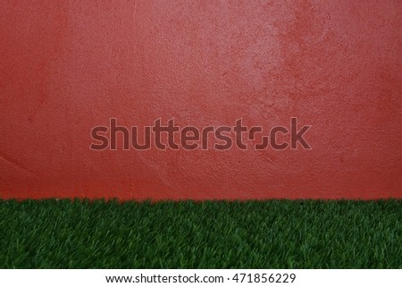 Red wall and green grass