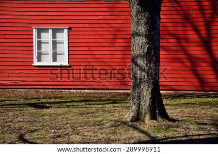Red wall of scandinavian house with white window and tree near by house - stock photo