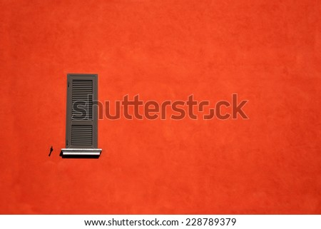 Red wall with gray window. Exterior of mediterranean design building in Italy. - stock photo