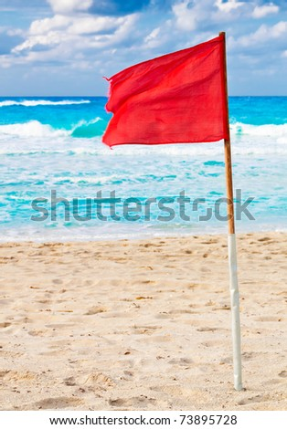 Red warning flag in a beach during a storm - stock photo