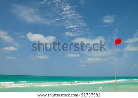 Red warning flag is a signal of strong wind, it  indicates a high hazard from surf and/or currents. Cuba beach. - stock photo
