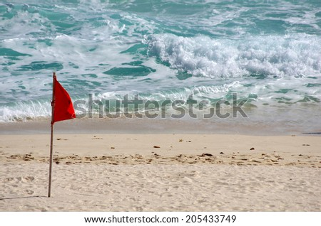 Red warning flag on the beach, Cancun, Mexico - stock photo