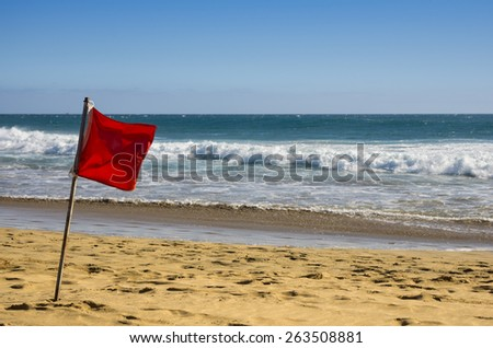 Red warning flag on the coast of Atlantic ocean, Gran Canaria, Canary islands, Spain - stock photo