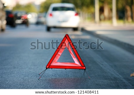 Red warning triangle with a broken down car - stock photo