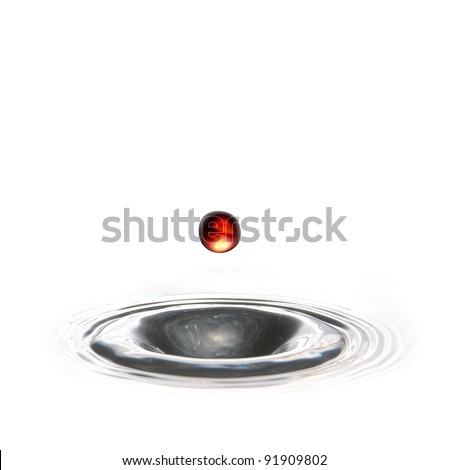 red water droplet falling into a hole of water - stock photo