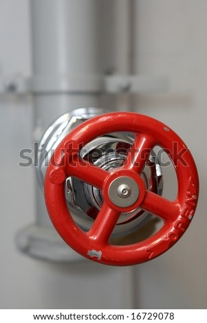 Red water pipe plumbing valve in factory - stock photo