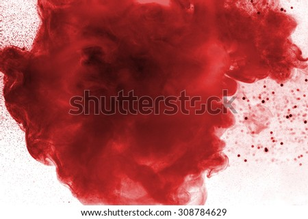Red watercolor in water with small pieces of paint. - stock photo