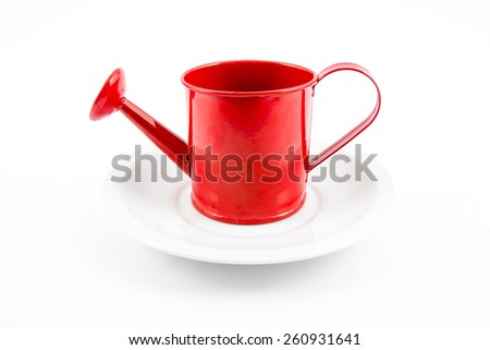 Red watering can of small pots on dish on white background - stock photo