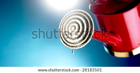 Red watering can with drop of water dripping out - stock photo