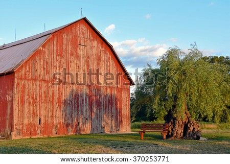 red weathered Michigan barn with tree shadow - stock photo
