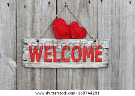 Red welcome sign hanging on wood door with two red hearts