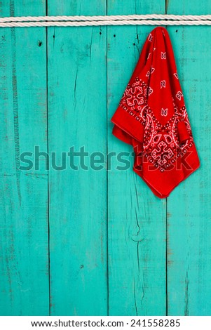 Red western bandanna or handkerchief hanging on blank antique teal blue rustic wooden background with white rope border - stock photo