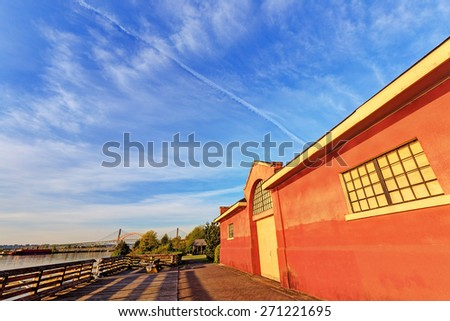 Red wharf warehouse lit by early morning sunlight, a historic building in SAPPERTON LANDING PARK, New Westminster, BC