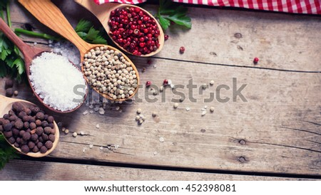 Red, white and allspice pepper and sea salt in wooden spoon on aged wooden background. Food ingredient. Selective focus. Place for text. Flat lay. Top view. Toned image. - stock photo