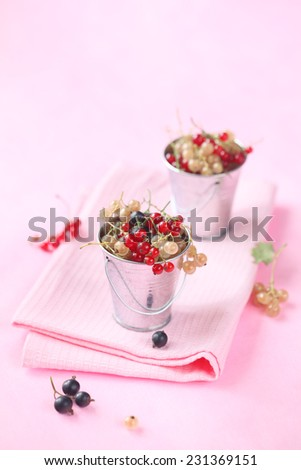 Red, White and Black Currants in two little buckets, on a pink napkin and light pink background. - stock photo