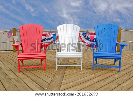 red, white and blue Adirondack chairs on wooden deck with American flags - stock photo